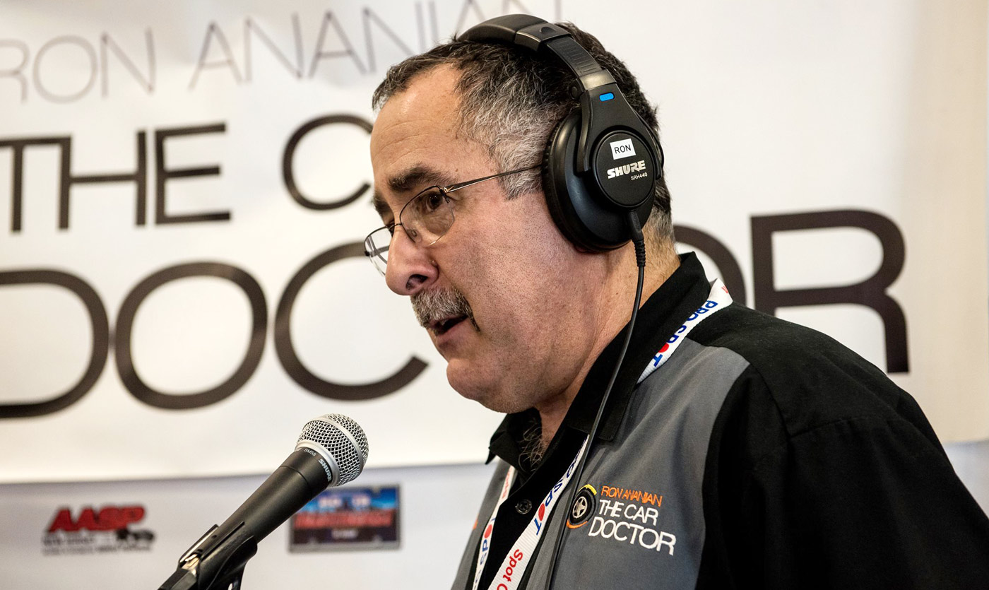 ron ananian on microphone in front of car doctor show banner